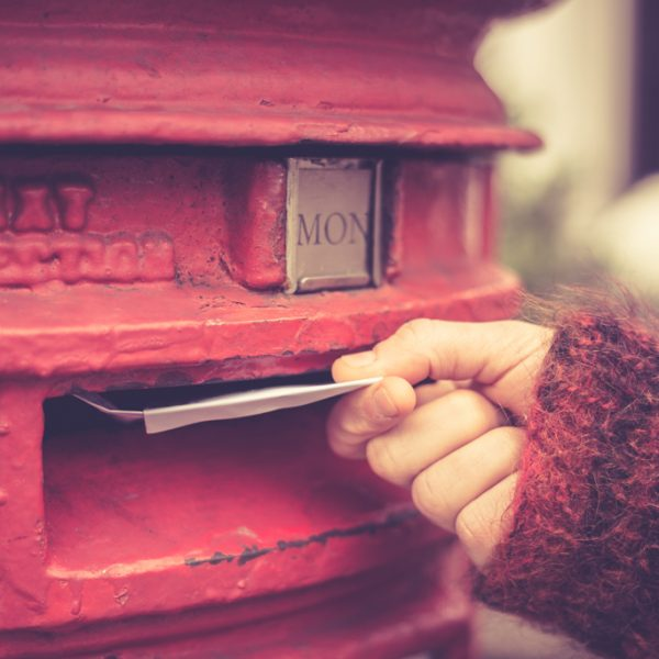 Woman putting letter in red mailbox